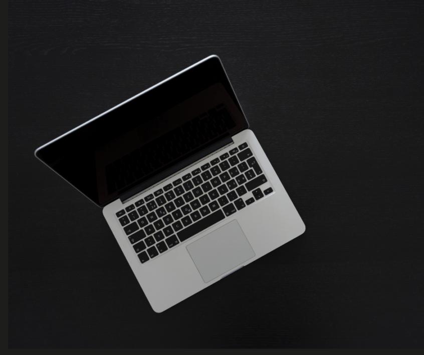apple laptop on a black background